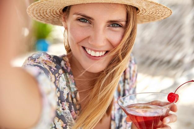Touristin genießt sommerferien, trinkt leckeren kalten cocktail mit kirsche dekoriert, macht foto von sich selbst oder selfie mit nicht erkennbarem gerät. sommertourismus, lifestyle und ruhekonzept