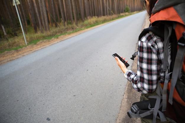 Touristin in einem karierten hemd mit einem orangefarbenen großen rucksack in der nähe einer autobahn im wald mit einem smartphone in der hand. navigation, satellitenkarten, kommunikation, inlandstourismus. backpacker, abenteuer