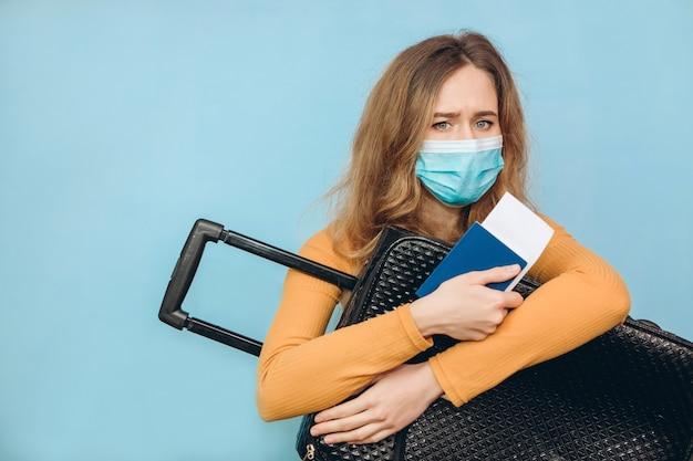 Touristin in einer medizinischen maske sitzt mit gepäck in den händen. covid-19-ausbruch des coronavirus. reise- und kronenkonzept. ein tourist kann wegen einer pandemie nicht abreisen.