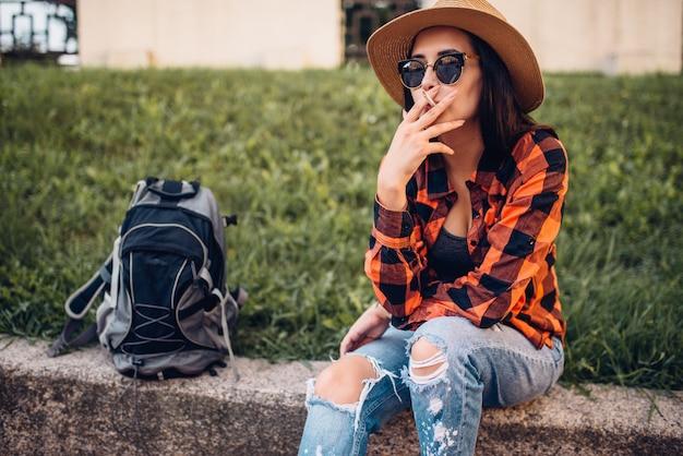 Touristin in hut und sonnenbrille rauchen zigaretten, pause während der tour. sommerabenteuer der jungen frau, stadtwandern