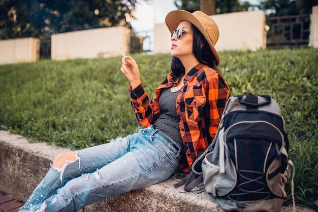 Touristin in sonnenbrillen rauchen zigaretten