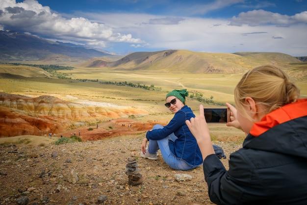 Touristin macht fotos von ihrer freundin auf dem smartphone an einem schönen aussichtspunkt