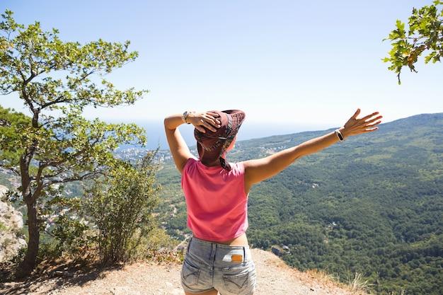 Touristin mit erhobenen händen schaut auf den panoramablick auf die bergspitze und freut sich, genießt es freiheit und abenteuer.