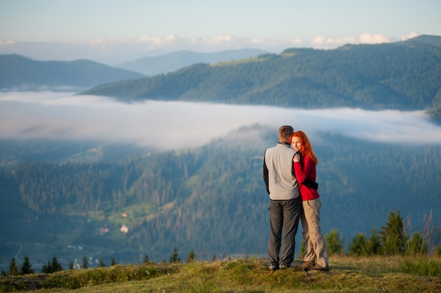 Touristische familie - mann und frau, die schöne berglandschaft mit morgendunst über den bergen und den wäldern umfassen und genießen. rothaariges mädchen, welches die kamera betrachtet