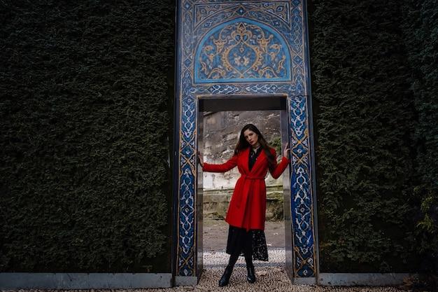 Touristische frau besucht den alten istanbul topkapi-palast. schöne junge frau in einem roten mantel betrachtet die wände des palastes von der seite des parks, istanbul