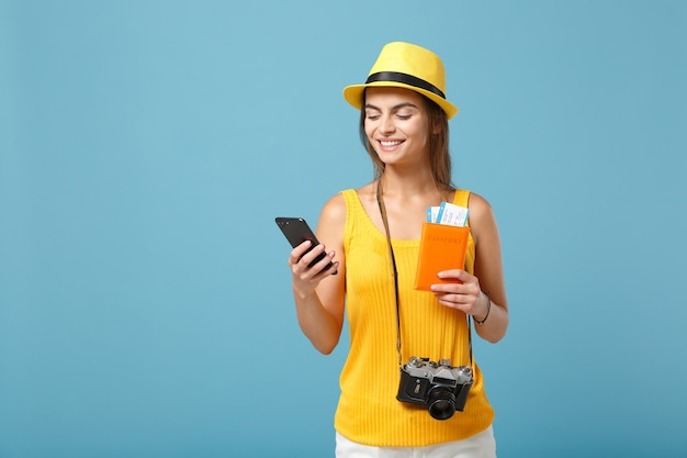 Touristische frau des reisenden im gelben freizeitkleidungshut, der kartenhandykamera auf blau hält
