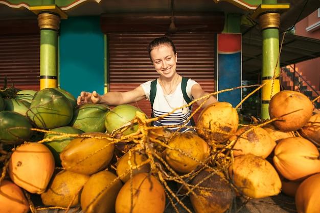 Touristische frau, die den lokalen asiatischen markt erkundet und glücklich ist, reife kokosnüsse zu sehen