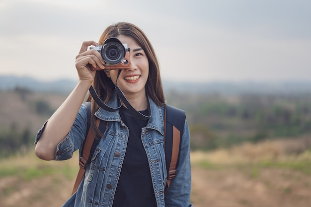 Touristische frau, die foto mit ihrer kamera in der natur macht