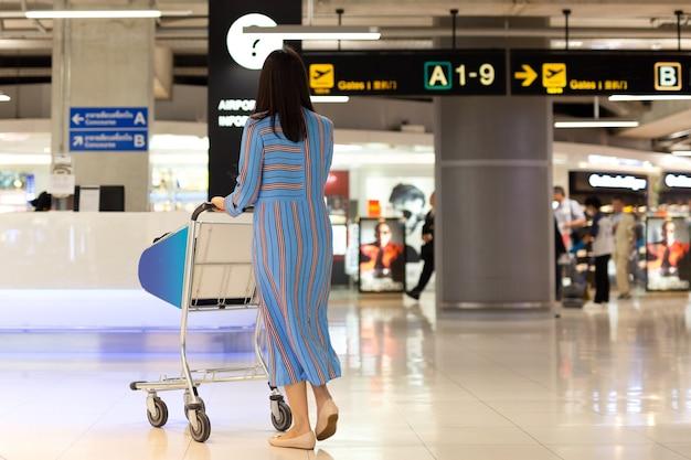 Touristische frau im flughafenabfertigungsgebäude, das nach abfahrt sucht