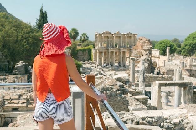 Touristische frau im roten hut, die die ansicht an der bibliothek von celsus bei ephesus, türkei genießt.