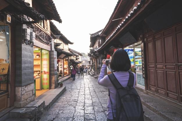 Touristische frau im urlaub, die foto auf der kamera macht