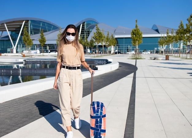 Touristische frau in der verrückten maske, die mit gepäck nahe flughafengebäude geht