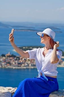 Touristische frau in einem weißen strohhut auf schöner blauer adria und gemütlichem inselhintergrund kroatien