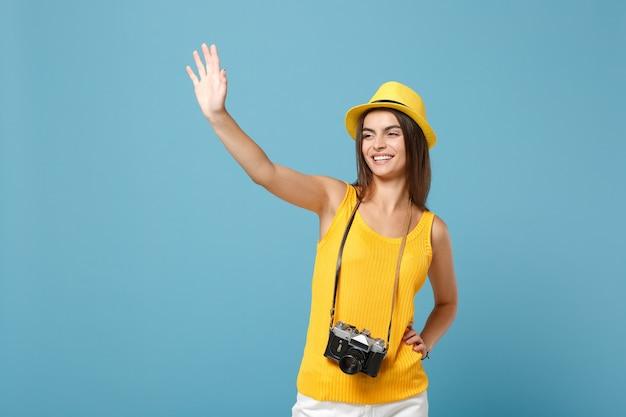 Touristische frau in gelber sommerkleidung und hut mit fotokamera auf blau