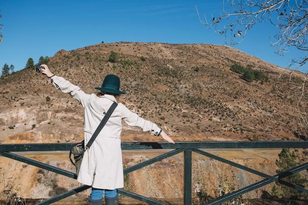 Touristische frau mit den händen auseinander am handlauf