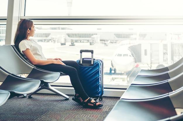Touristische frauen, die telefon am wartebord des internationalen flughafens verwenden