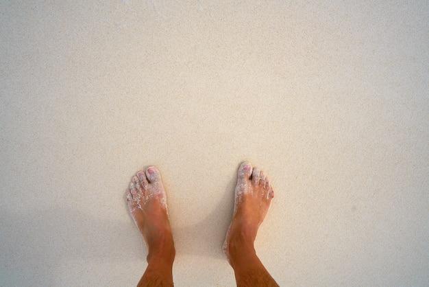 Touristische füße im tropischen weißen sandstrand