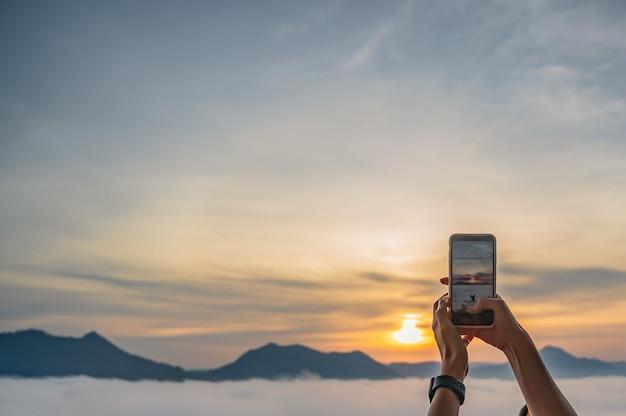 Touristische hand mit handy fotografieren sie den sonnenaufgang und das nebelmeer auf phu thok in chiang khan am frühen morgen. chiang khan ist eine altstadt und ein sehr beliebtes ziel für thailändische touristen