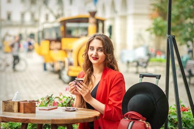 Touristische junge kaukasische frau in roter jacke mit kaffeetasse am tisch im café im freien