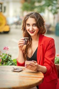 Touristische junge kaukasische frau in roter jacke mit kaffeetasse am tisch im café im freien.