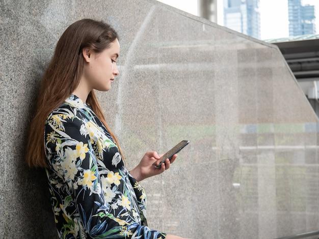Touristische kaukasische frauenlesetextnachricht oder anwendung des smartphone