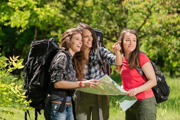 Touristische mädchen im wald mit karte und rucksäcken