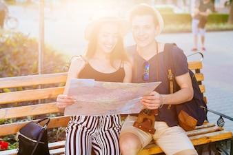 Touristische Paare auf Bank mit Sonnenschein