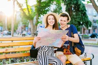 Touristische Paare auf der Bank, die Karte betrachtet
