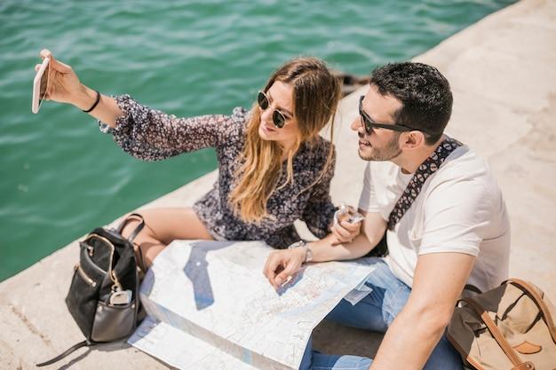 Touristische paare, die auf ansteckendem selbstporträt der anlegestelle am handy sitzen