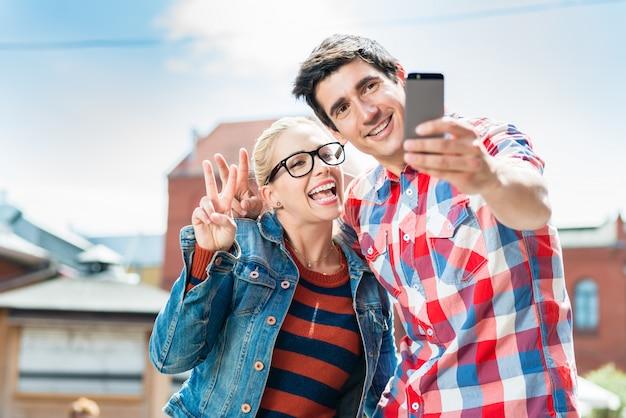 Touristische paare, die selfie auf dachspitze in berlin nehmen