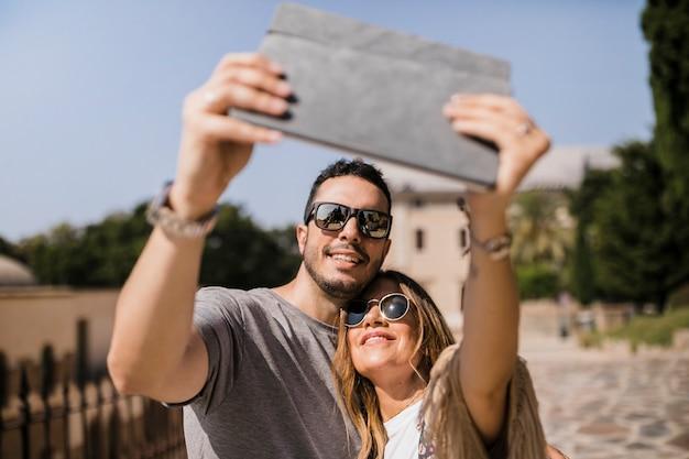 Touristische paare, die selfie auf digitaler tablette nehmen