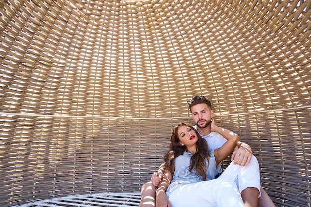 Touristische paare entspannten sich innerhalb eines strandsonnenschirms