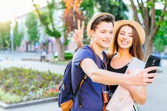 Touristische Paare im Park, der für selfie aufwirft