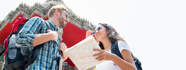 Touristische paarwanderer, die in thailändischen tempel auf sommerferien in bangkok reisen