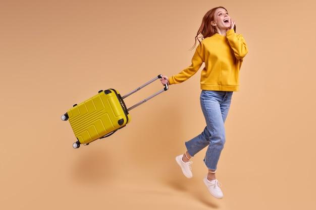 Touristische rothaarigefrau des reisenden mit koffer, die im lässigen outfit einzeln im studio springt. kaukasische passagierin, die an wochenenden ins ausland reist. flugreisekonzept. platz kopieren