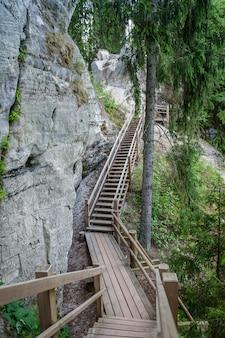 Touristische spur mit hölzerner wegstrecke und treppe nahe sandsteinklippen. die klippe von sietiniezis, lettland. gauja-nationalpark.