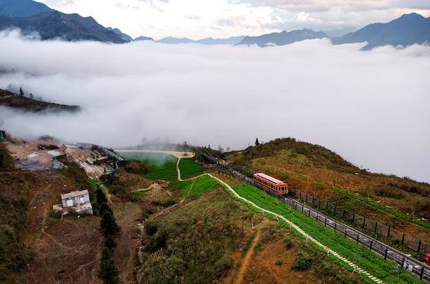 Touristische straßenbahn in sapa city zum berg fansipan, straßenbahn fansipan, sapa, lao cai, vietnam. roter waggon im nebel hoch in den bergen über den wolken