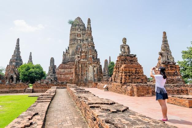Touristische teenager-mädchen machen ein foto alte pagode von wat chaiwatthanaram ist buddhistische tempel berühmte touristenattraktion religion im ayutthaya historical park, phra nakhon si ayutthaya, thailand