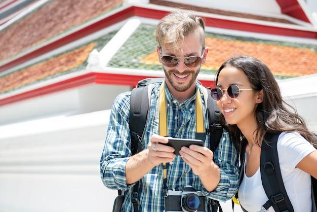 Touristische wanderer, die smartphoneschirmfindungsrichtung beim reisen in thailand betrachten