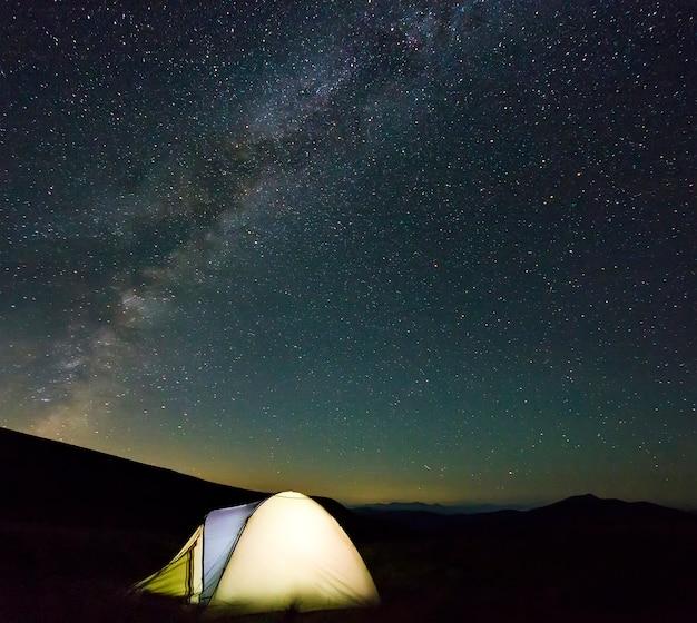 Touristische wanderer zelten nachts in den bergen mit milchstraßensternen am himmel