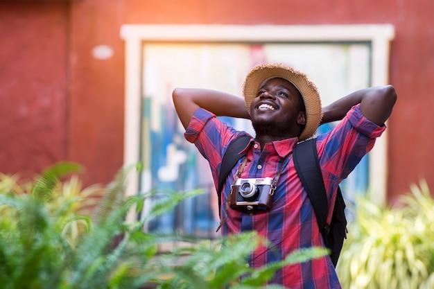 Touristischer afrikanischer mann fühlen sich mit reiseplatz in der landschaftsstadt glücklich.