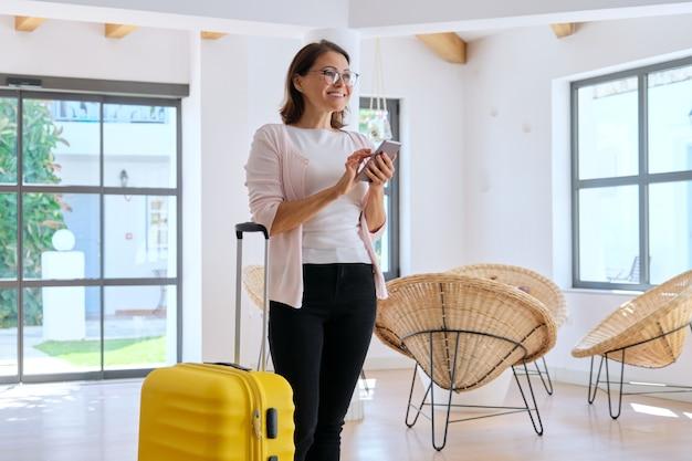 Touristischer hotelgast der frau mit koffer in der lobby des hotels mit smartphone. reisen, urlaub, freizeit, geschäftsreise, leute