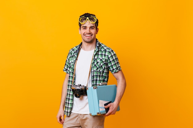 Touristischer kerl, der kariertes hemd und weißes t-shirt trägt kamera betrachtet. porträt des mannes mit tauchmaske auf seinem kopf, retro-kamera und handkoffer haltend.