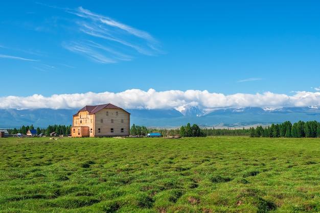 Touristischer komplex, hölzernes gästehaus vor dem hintergrund schneebedeckter hochgebirge.