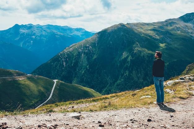 Touristischer mann, der auf die oberseite des berges steht