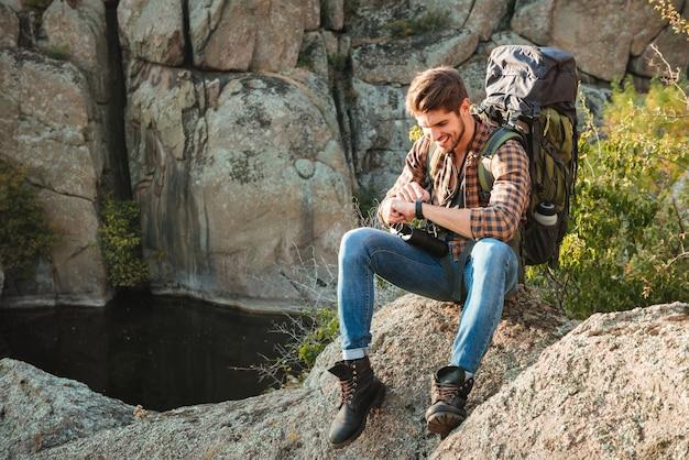 Touristischer mann, der auf felsen sitzt und armbanduhr nahe der schlucht betrachtet