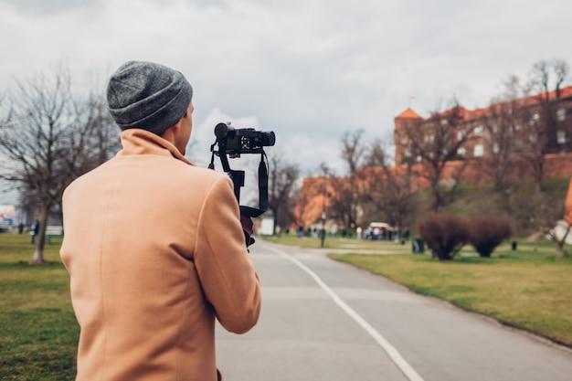 Touristischer mann, der filmmaterial unter verwendung des steadicam-stabilisators mit kamera filmt, die wawel-schloss in krakau polen filmt.