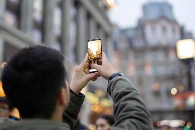 Touristischer mann, der fotos mit handy mit gebäude macht