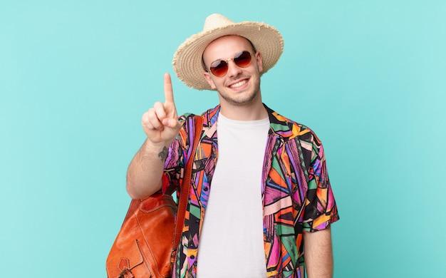 Touristischer mann, der lächelt und freundlich aussieht, nummer eins oder zuerst mit der hand vorwärts zeigend, herunterzählend