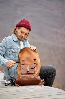 Touristischer mann, der ledernen braunen rucksack während der wanderung in den bergen öffnet, seitenansicht